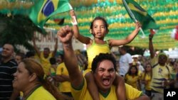 FILE - Soccer fans celebrate as they watch on a big screen television, the second goal scored by Brazil's Neymar in the World Cup match against Cameroon, in Manaus, Brazil.