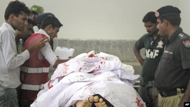 Policemen, rescue workers and the media stand next to the body of the Saudi diplomat who was killed by unidentified gunmen, at a morgue in Karachi's Jinnah hospital, May 16, 2011