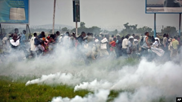 'Union for Democracy and Social Progress' supporters flee after tear gas canisters were used by police to disperse them near Ndjili airport in Kinshasa, DRC, November 26, 2011.