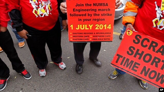 Members of the National Union of Metal Workers of South Africa, NUMSA, hold banners as they protest with others during national strike action in Cape Town, South Africa,  July 1, 2014.