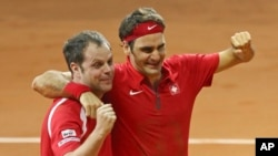 Swiss coach Severin Luthi (L) and Switzerland's Roger Federer celebrate after Federer defeated France's Richard Gasquet in the Davis Cup final in Lille, northern France, Nov. 23, 2014.