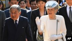 FILE - Japan's Emperor Akihito (left) and Empress Michiko walk into the compound of the memorial house of Vietnam's nationalist Phan Boi Chau (1867-1940), in the central city of Hue, Vietnam's former imperial city, March 4, 2017.