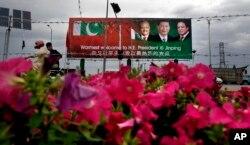 巴基斯坦街道上欢迎习近平的公告牌上有中国主席习近平、巴基斯坦总统马姆努恩·侯赛因和总理谢里夫的肖像(2015年4月19日)