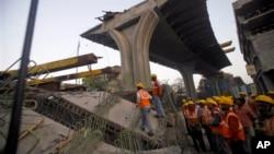Regu penyelamat berdiri di dekat jembatan yang runtuh di Mumbai, India, 7 Februari 2013. (AP Photo/Rafiq Maqbool). Tiga orang dilaporakn tewas dalam insiden ini.