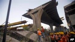Nhân viên cứu hộ đứng cạnh đống đổ nát của một cây cầu bị sập ở Mumbai, Ấn Độ, ngày 7/2/2013.