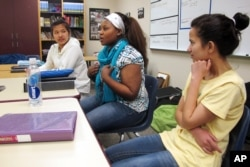 FILE - Nakafu Kahasha, center, describes her short story about her journey from Congo to Tanzania to Fargo, N.D., nearly six years ago, while Nepal natives Anju Tamang, left, and Anju Gurung listen during their English-language learners class at Fargo South High School, Jan. 26, 2016.