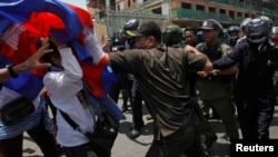FILE: Protesters clash with police as they attempt to go toward the Phnom Penh Municipal Court, in central Phnom Penh April 25, 2014.