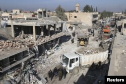 Residents inspect damage at a site hit by one of three explosive trucks, in the YPG-controlled town of Tel Tamer, Syria, Dec. 11, 2015.