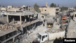 Warga memeriksa kerusakan pasca ledakan bom truk di kota Tel Tamer, Suriah Jumat (11/12).