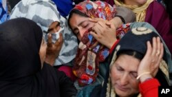 An unidentified relative is comforted by Kashmiri villagers as she grieves near the dead body of Sarjeel Sheikh, a civilian who was shot during a protest near the site of gunbattle in Khudwani village, south of Srinagar, Indian controlled Kashmir, April. 11, 2018.