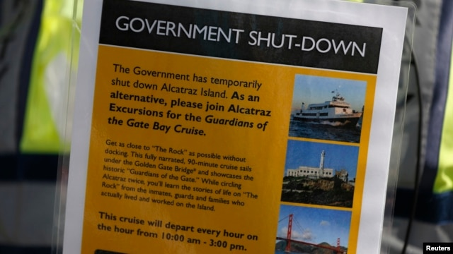 A security officer holds a sign informing people on the government shutdown of Alcatraz Island, a tourist attraction operated by the National Park Service, in San Francisco, California, Oct. 1, 2013.