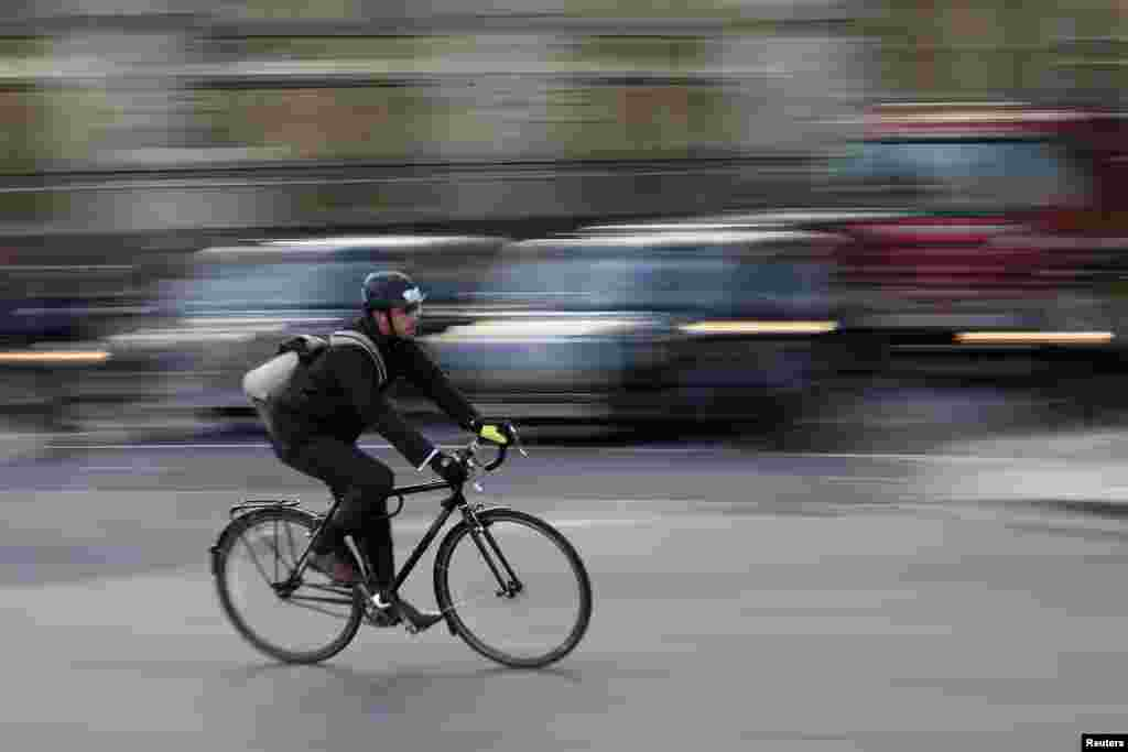 A Commuter cycles in central London. The deaths of five cyclists in just nine days on the roads this month in London have prompted calls for the city's mayor Boris Johnson to speed up road safety measures in the capital. The fatalities have been caused through collisions with buses, trucks and a coach.