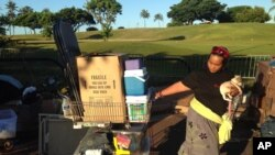 Seorang perempuan tunawisma membawa anjing dan barang-barangnya setelah tempat tinggalnya dibongkar pemerintah Honolulu.