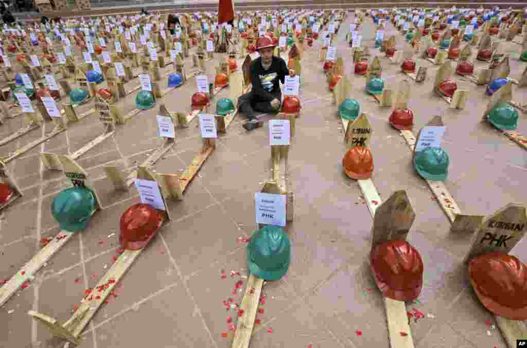 An activist of National Solidarity of Mine Workers sits among mock graves of miners during a protest against the government's plan to ban raw mineral exports that will take effect this month, in Jakarta, Indonesia.