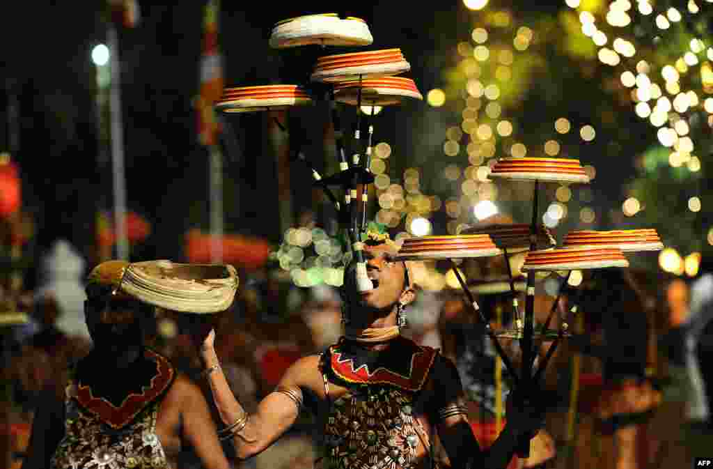 Sri Lankan traditional dancers perform in front of the Gangarama Temple during the Navam Perahera festival in Colombo, Feb. 3, 2015.