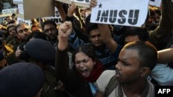 Indian residents hold placards and chant slogans as they take part in a protest against the alleged rape of a passenger by a driver working for the Uber taxi company in New Delhi, Dec. 7, 2014.