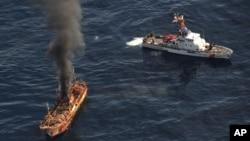 Una columna de humbo se eleva del barco fantasma japonés que fue hundido ayer por la Guardia Costera de EE.UU.