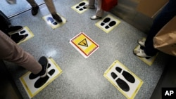 Social distancing stickers are viewed in an elevator at a shopping building Monday, Sept. 28, 2020, in Tokyo.