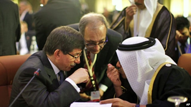 Turkey's FM Ahmet Davutoglu (L) confers with United Arab Emirates' (UAE) FM Sheikh Abdullah bin Zayed al-Nahyan during the Friends of Syria Conference in Tunis, February 24, 2012