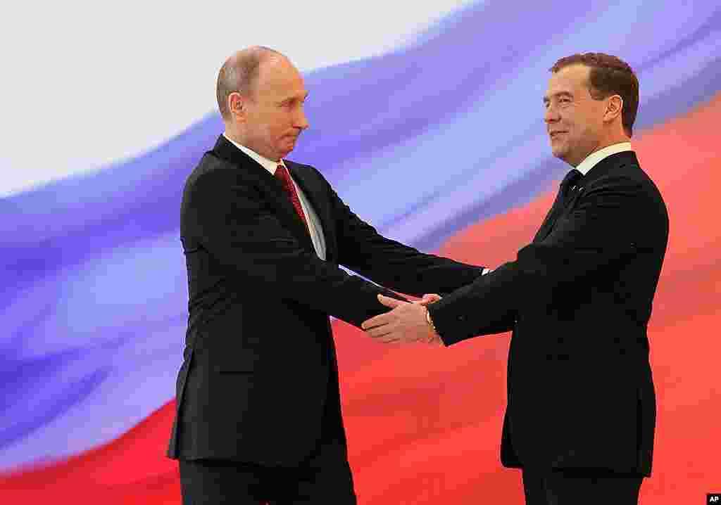 ປະທານາທິບໍດີ Vladimir Putin, ຊ້າຍ, ກັບອະດີດປະທານາທິບໍດີ Dmitry Medvedev ຈັບມືກັນ ໃນພິທີສາບານໂຕ. (AP)