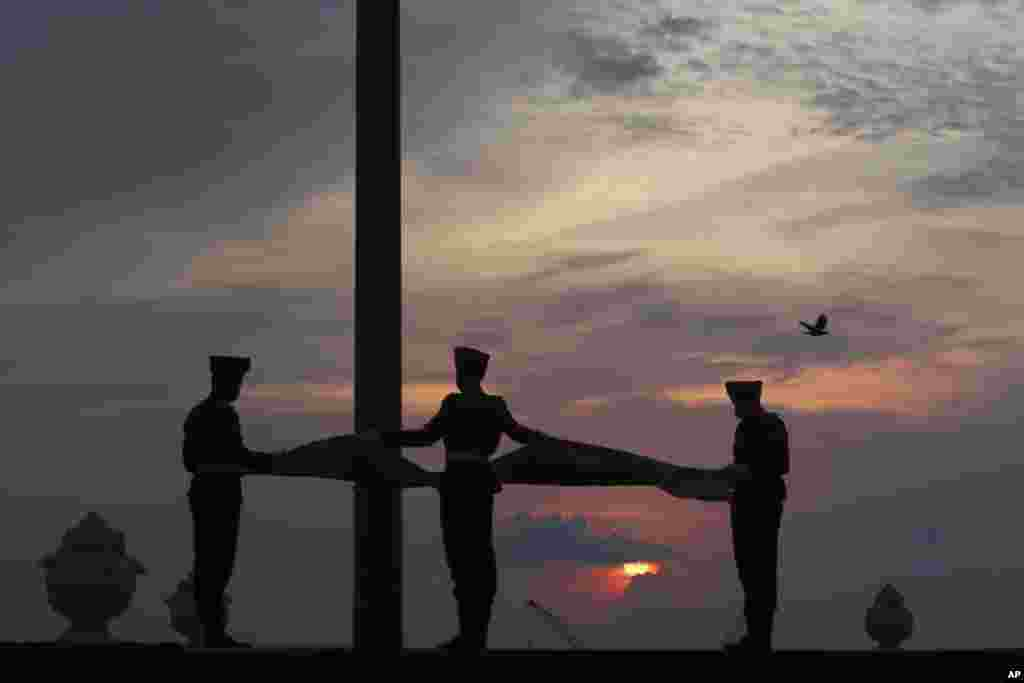 Sri Lankan Army soldiers lower the national flag as the sun sets in Colombo.