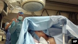 Dr. Alistair Fyfe (kiri) sedang bersiap untuk memasang implan untuk alat pacu jantung unntuk James Thompson (81 tahun) di Medical City Hospital, Dallas (Foto: dok). Para periset di Cedars-Sinai Heart Institute di Los Angeles menciptakan alat pacu jantung alami dengan menyisipkan gen tunggal yang disebut Tbx18.