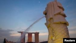 Patung Merlion menghadap ke resor dan kasino Marina Bay Sands di Singapura.