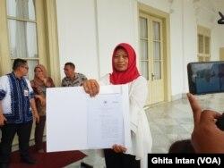 Baiq Nuril memperlihatkan salinan amnesti dari Kemenkumham kepada awak media, di Istana Keprsidenan Bogor, Bogor, Jumat, 2 Agustus 2019. (Photo: VOA/Ghita).