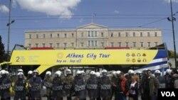 Bus touris melewati gedung parlemen Yunani sementara polisi membuat barikade bagi para demonstran di Athena.