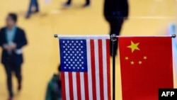 This file picture taken on November 6, 2018 shows a Chinese and US flag at a booth during the first China International Import Expo in Shanghai. - The US public's opinion of China has plummeted amid a surge in strategic and trade tensions in recent years