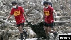 Nhân viên cứu hộ kéo bao chứa xác các nạn nhân thiệt mạng trong trận bão Bopha tại thị trấn New Bataan, nam Philippines, 7/12/2012