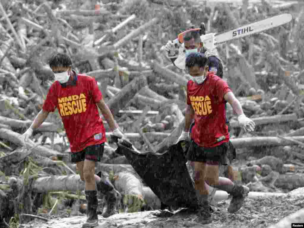 Rescuers carry a body bag containing bodies of typhoon victims recovered from the debris swept by floodwaters at the height of Typhoon Bopha, in New Bataan town in Compostela Valley, southern Philippines December 7, 2012. Residents in the southern Philipp