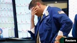 Un operador de bolsa en Wall Street reacciona abatido ante el desplome de las acciones.