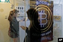 People use a Bitcoin ATM in Hong Kong, Friday, Dec. 8, 2017.