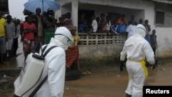 Trabajadores de la salud van casa por casa en la capital de Liberia para encontrar infectados por ébola.