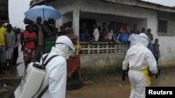 Petugas kesehatan Liberia dengan menggunakan pakaian pelindung berusaha mengevakuasi jenazah korban ebola di Monrovia (foto: dok).