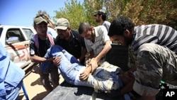 ນາຍແພດລີເບຍແລະພວກນັກລົບກະບົດຊ່ອຍກັນຫາມນັກລົບຄົນນຶ່ງ ທີ່ໄດ້ຮັບບາດເຈັບທີ່ໂຮງໝໍສະໜາມແຫ່ງນຶ່ງ ໃກ້ໆເຂດແນວໜ້າ ທາງກໍ້າຕາເວັນຕົກຂອງເມືອງ Misrata (10 ມິຖຸນາ 2011)