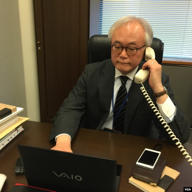 Tomohiko Taniguchi, Adviser to Cabinet of Prime Minister Abe, speaks on the phone in Tokyo, Feb. 8, 2016. (S. Herman/VOA)