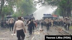 Mobil water canon Polda Sulawesi Tengah menyemprotkan air untuk membubarkan kerumunan mahasiswa yang sedang melakukan pelemparan batu kearah petugas dalam aksi unjuk rasa penolakan UU Cipta Kerja, Kamis, 8 Oktober 2020. (Foto: VOA/Yoanes Litha)