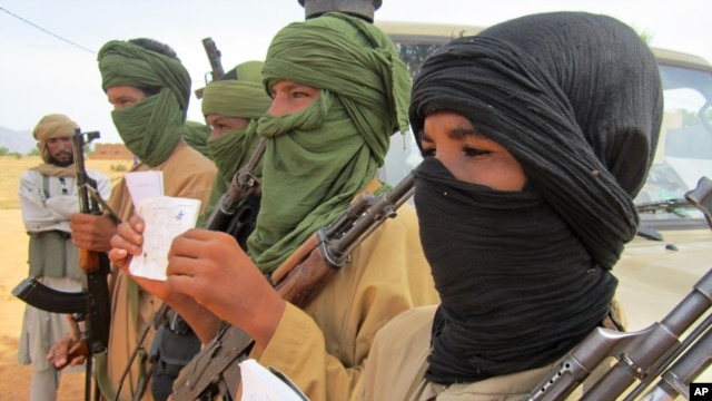 FILE - Young fighters display their Quranic studies notes for a journalist as their Islamist commanders look on, in Douentza, Mali.