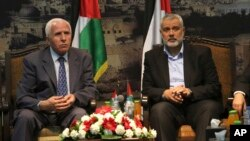 FILE - Gaza's Hamas Prime Minister Ismail Haniyeh, right, and senior Fatah official Azzam al-Ahmad meet in Gaza for talks aimed at reaching a reconciliation agreement between the two rival Palestinian groups, Hamas and Fatah on April 22, 2014.