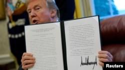 Presiden Amerika Donald Trump berbicara kepada wartawan setelah menandatangani peraturan pemberlakuan bea masuk untuk impor mesin cuci dan solar panel, di Oval Office, Gedung Putih, Washington, 23 Januari 2018.
