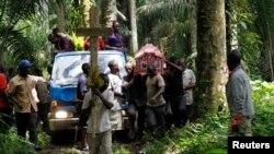 Des parents et amis portent le corps d'Yvonne Masika tuée lors d'une attaque perpétrée par des présumés rebelles de l'ADF-NALU, ils se dirigent au lieu de l'enterrement dans un village près de Beni Mbau, dans la province du Nord-Kivu, en RDC, le 21 octobre 2014.