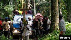 FILE - Relatives and friends carry the body of Yvonne Masika, who was killed during an attack by suspected ADF-NALU rebels, for burial in Mbau village near Beni, in North Kivu province, D.R.C., Oct. 21, 2014.