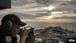 Seorang petugas pengawas pantai, Jacob Williams, menggunakan teleskop untuk mengamati kapal induk USS Carl Vinson (CVN 70) dan Carrier Strike Group (CSG) 1 mendekati Surigao Strait, FIlipina (Foto: dok).