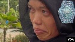 Một phụ nữ ở Banda Aceh nhìn chồng của bà bị bằng roi vì đánh bạc, 5/12/14
