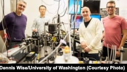 This instrument built by UW engineers (from left) Peter Pauzauskie, Xuezhe Zhou, Bennett Smith, Matthew Crane and Paden Roder (unpictured) used infrared laser light to refrigerate liquids for the first time.Dennis Wise/University of Washington