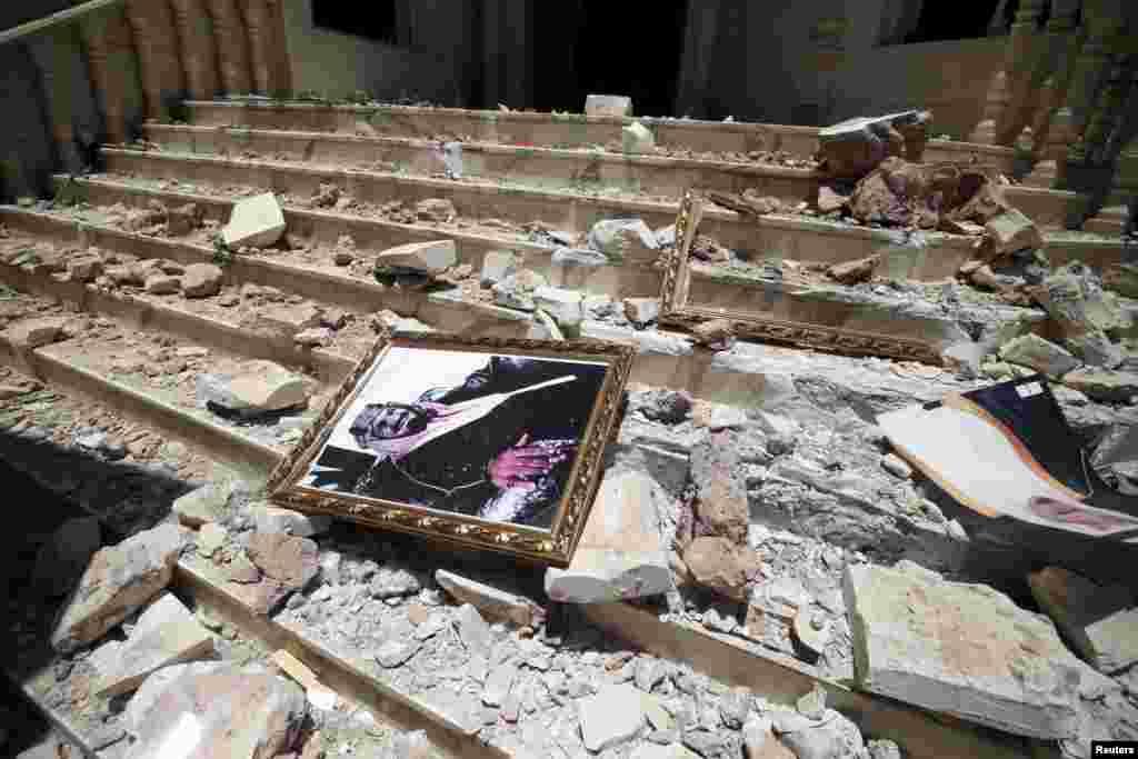 Foto Raja Saudi, Salman bin Abdulaziz, tergeletak di antara puing-puing kantor pusat Pusat Budaya Saudi yang hancur akibat serangan udara di Sana'a, Yaman (21/4). (Reuters/Mohamed al-Sayaghi)