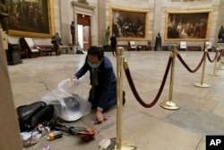 Rep. Andy Kim, D-N.J., cleans up debris and personal belongings strewn across the floor of the Rotunda in the early morning hours of Thursday, Jan. 7, 2021, after protesters stormed the Capitol in Washington, on Wednesday.