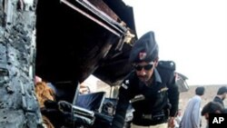 Pakistani security officials collect evidence near a vehicle targeted by a suicide attacker in Kohat, 60 kilometers south of Peshawar, Pakistan, Dec. 8, 2010.